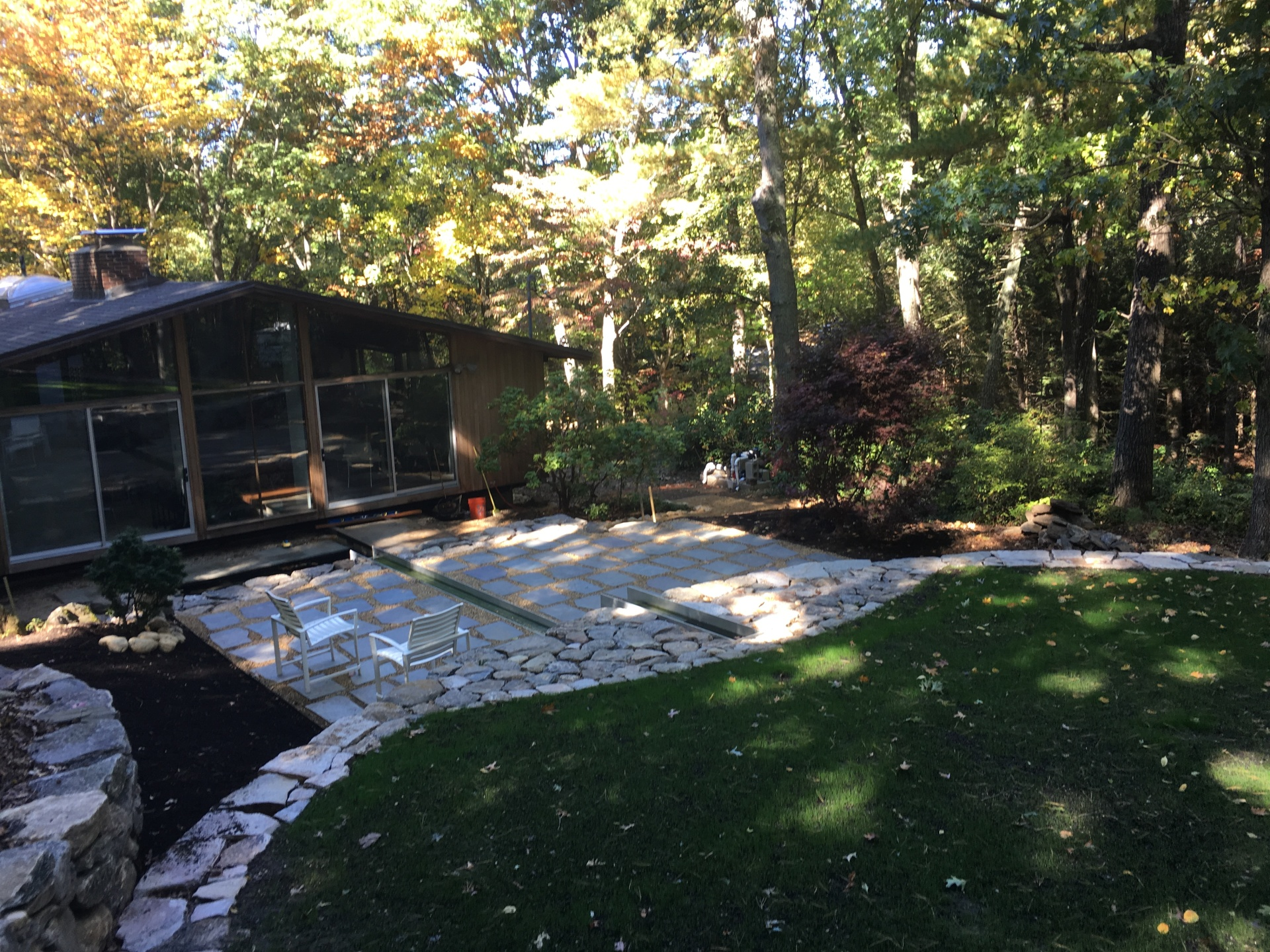 Modernist woodland home with elegant channel of water running through a patio,