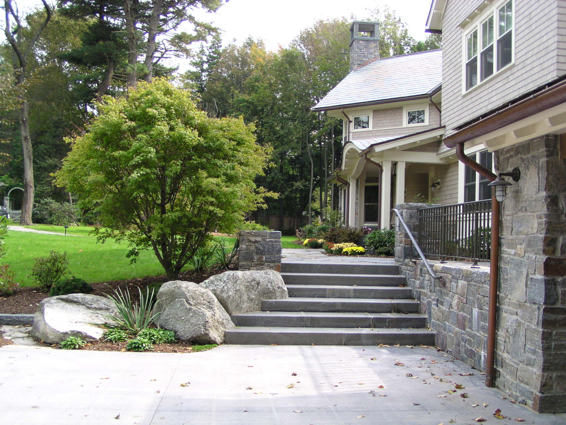 granite stairs, boulder and japanese maple frame the walkway to the front door.