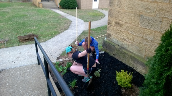 Zoe Roberson (left) and Hannah Hubert (right) spreading mulch.