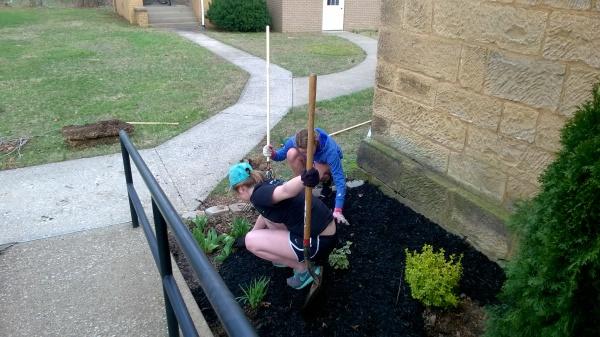 Zoe Roberson (left) and Hannah Hubert (right) spreading mulch.