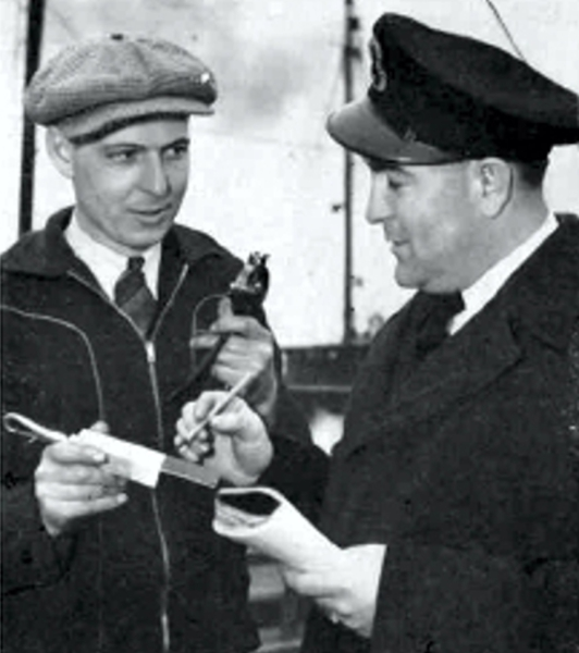 "There are 10 fuel compartments on the ""Norwood Park"", Gauger George Hoskin, of Halifax Refinery, is discussing the fuel load with Chief Stoker Donald Conron of the Royal Canadian Navy."