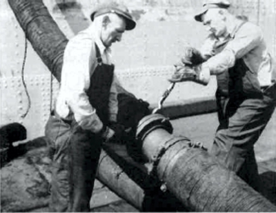 The cargo hose is bolted up. It is being used here to fill the cargo tanks of a merchant aircraft carrier.