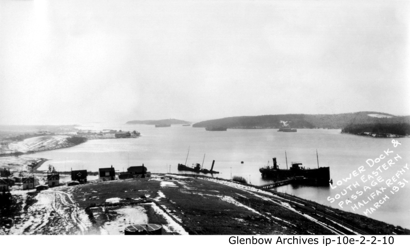 Looking east, lower dock at Dartmouth's Imperial Oil  Refinery, Avenue B Imperoyal Village in the background. Photographed in March 1931.