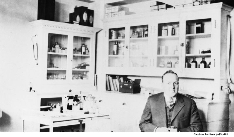 Doctor F. Malcolm, visiting physician, in first-aid room of Imperial Oil refinery Dartmouth 1920
