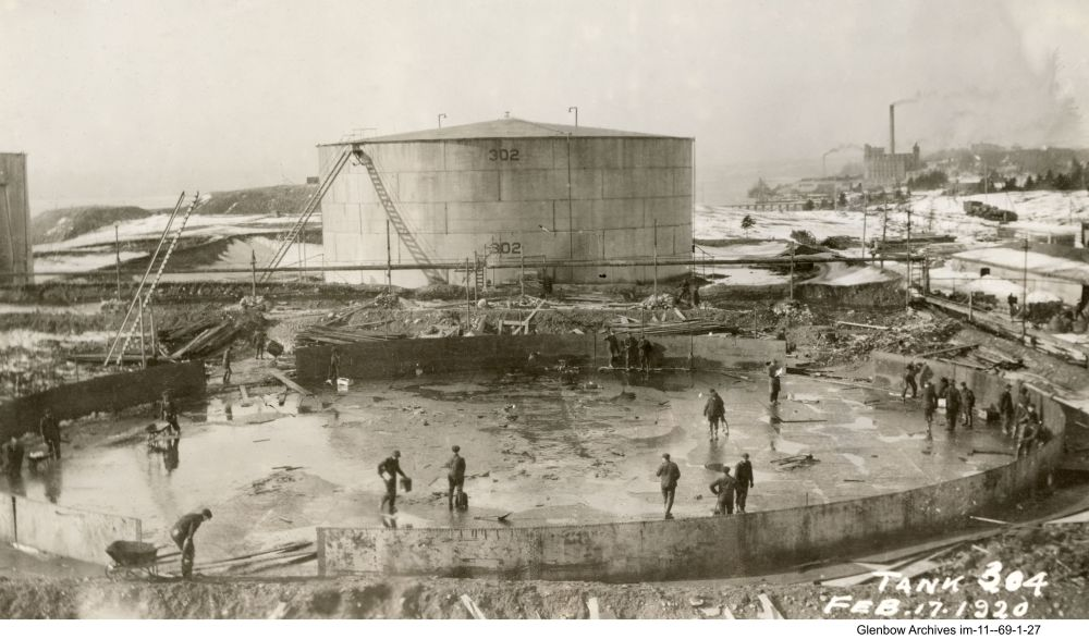 tank 304 under construction, Imperial Oil's Imperoyal Refinery, Dartmouth, February 17, 1920, Acadia Sugar Refinery in the background