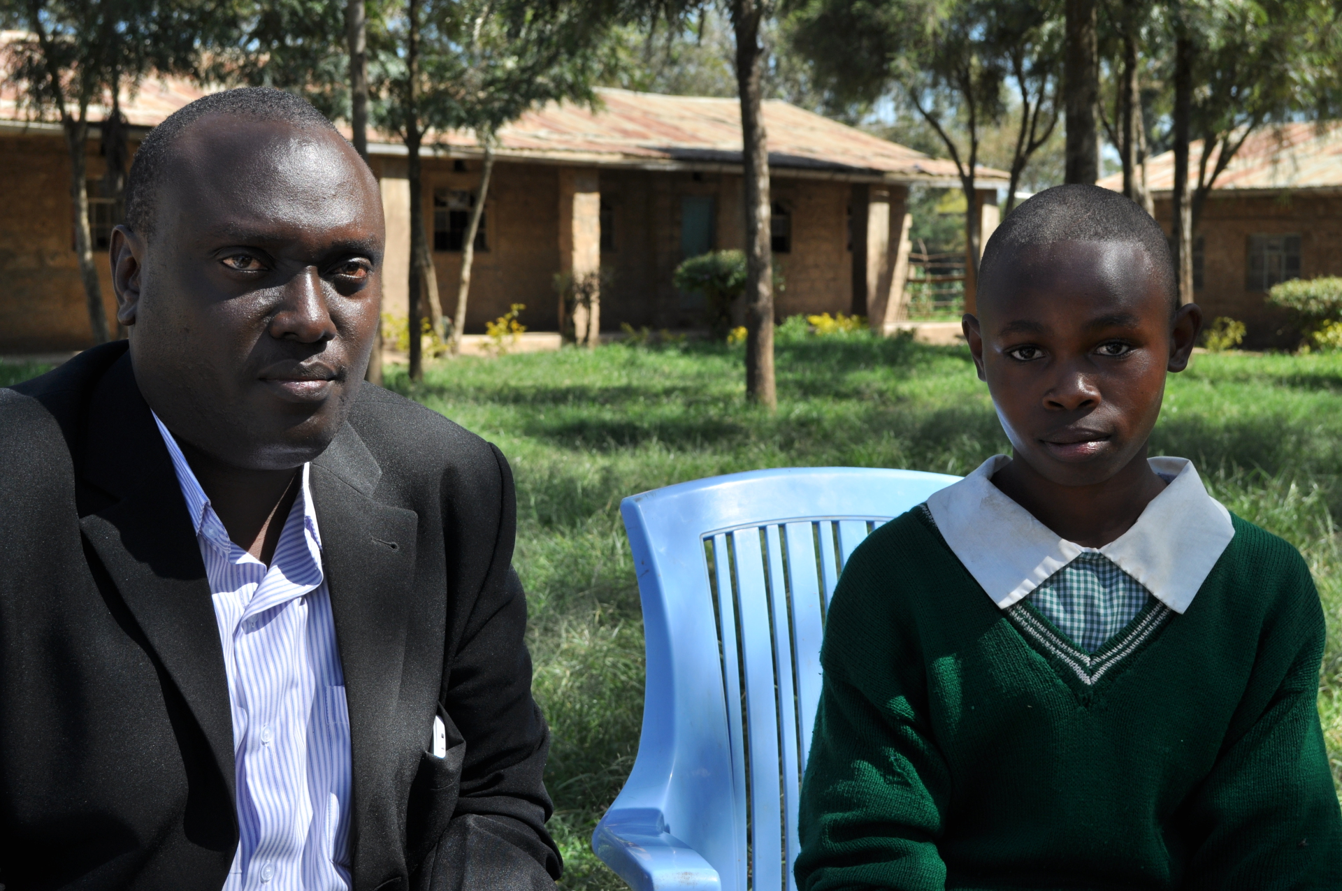 ASN Upendo Village Child Welfare Officer, Samuel Maina, with sponsored student at Nyondia Primary School.