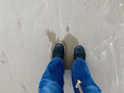 bottes sur la plage, pieds dans la mer