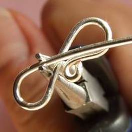 Use the tip of your pliers and grip the wire where it connects with the bottom prong
