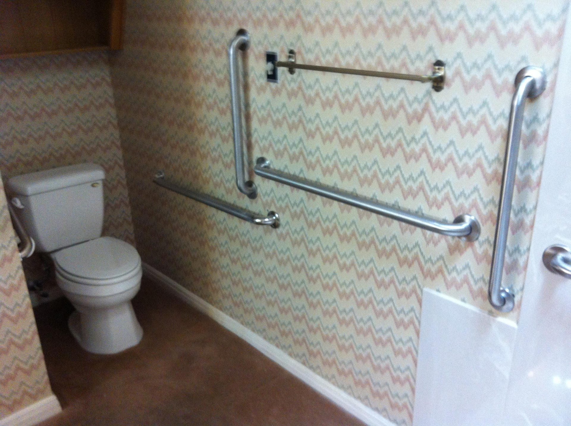Handicap toilet with extra bars for wheelchair person