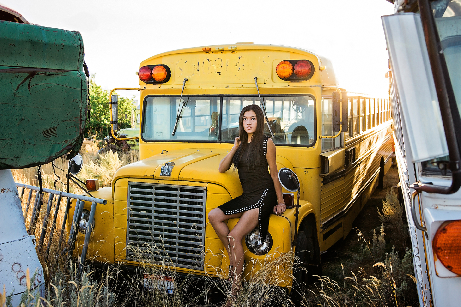 This photo shoes a model posing in front of a school bus in a car graveyard.