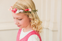 A sweet flower girl looks softly downwards as the wind blows gently through her hair.