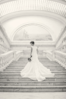 A black and white photo of a bride in her dress on a beautiful grand staircase.