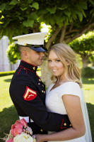 A marine and his bride stand in front of a tree on their wedding day. The bride smiles at the camera while the groom smiles lovingly at the bride.