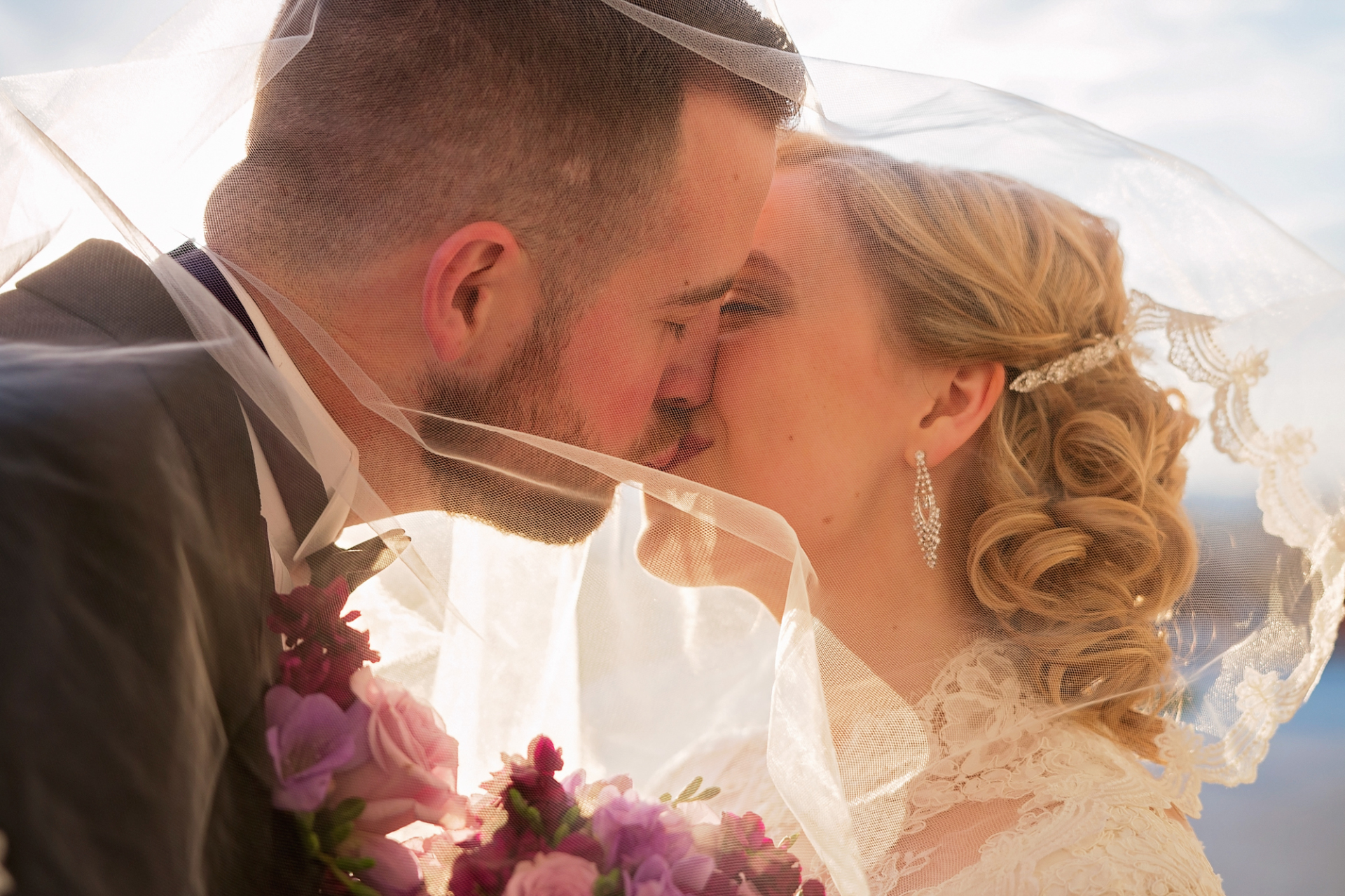 A bride and groom kiss romantically underneath the bride's veil at the Utah State Capitol.