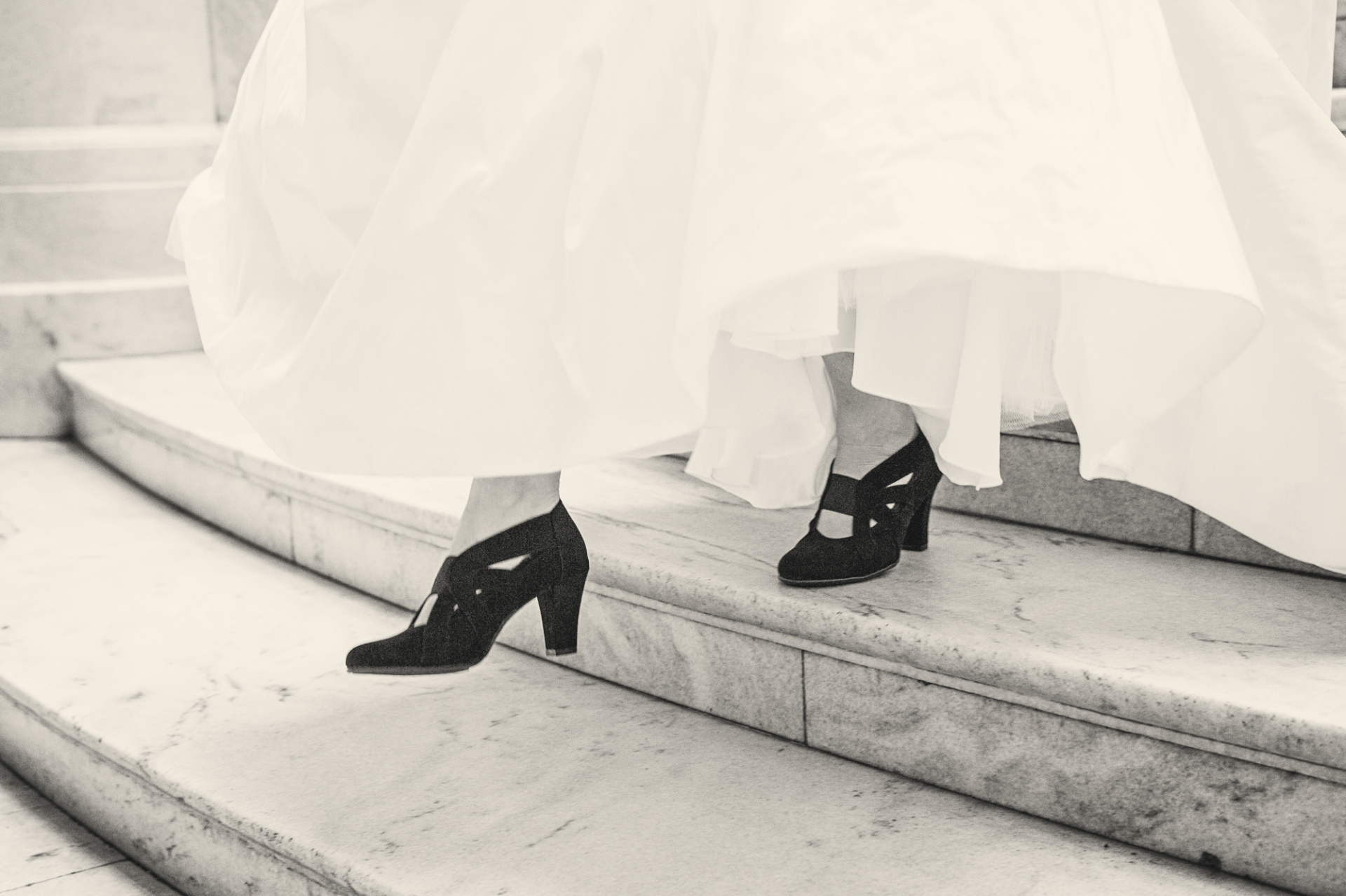 A bride shows off her shoes underneath her dress while walking down a staircase.
