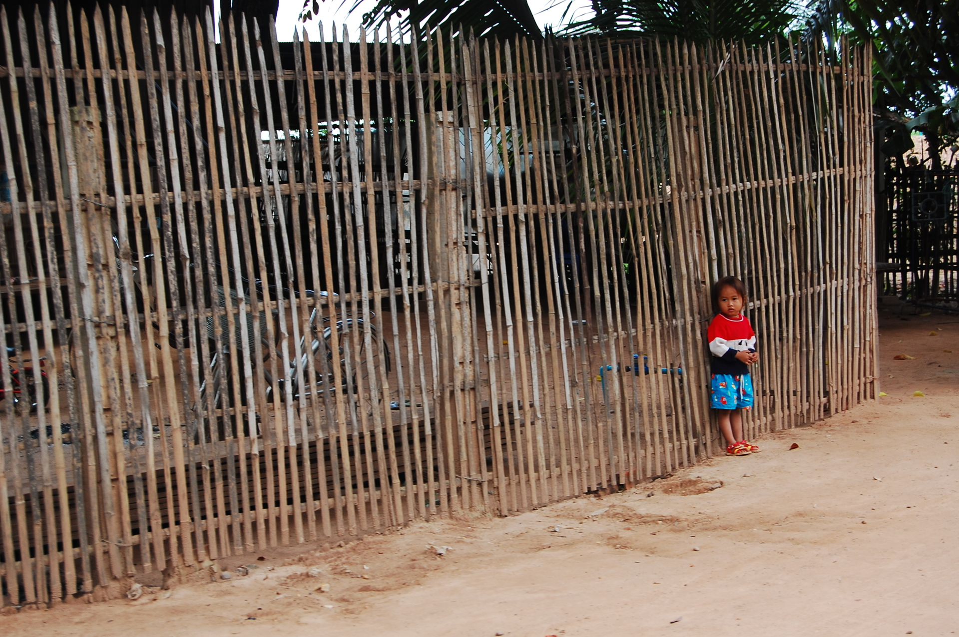 Girl standing against a fence