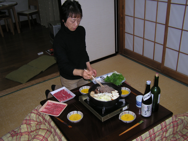 Mayu's mother Naoe prepares dinner at the table. Japan: annmariemershon.com