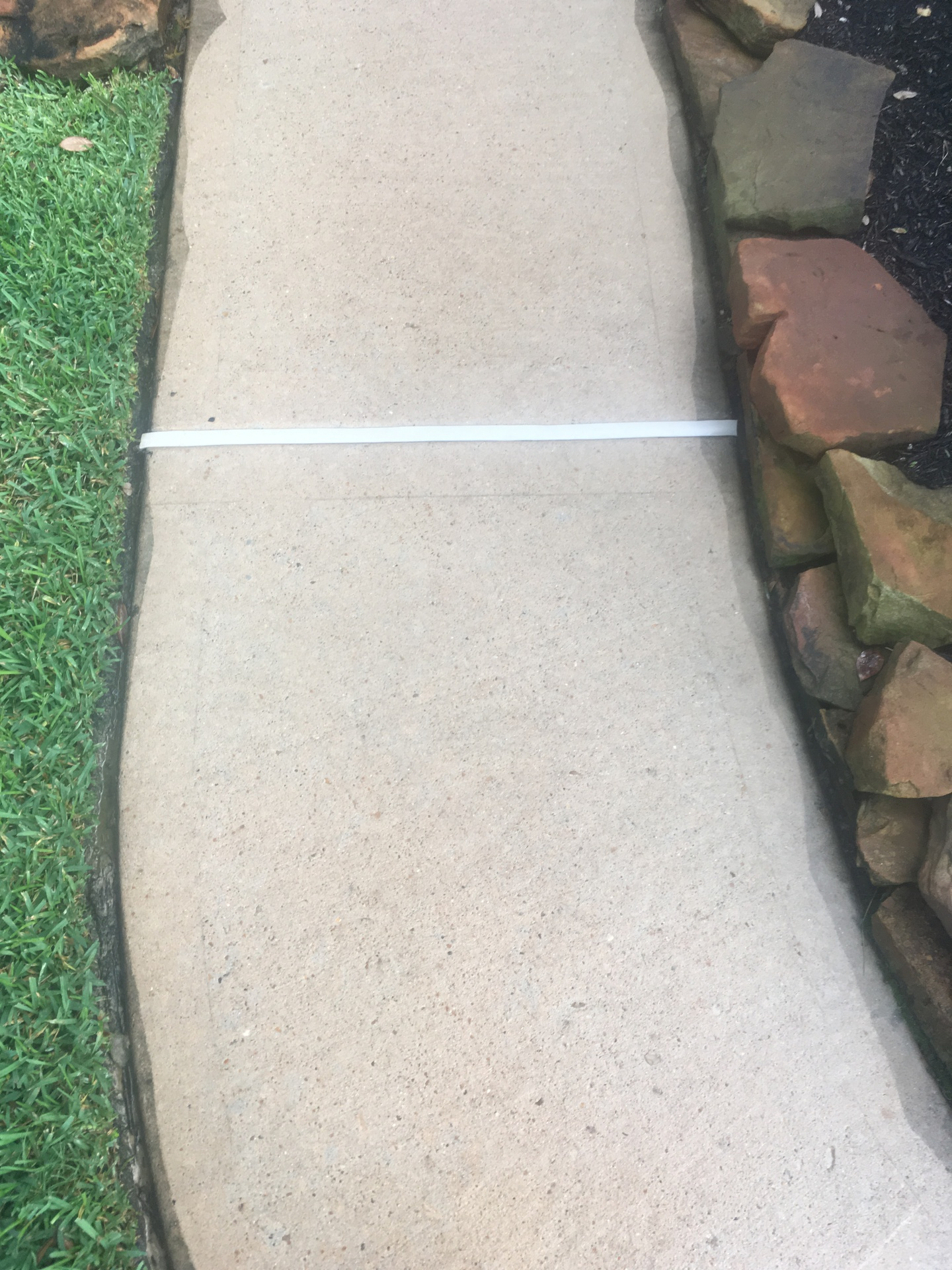 Pressure washed concrete and newly installed Trim-A-Slab expansion gap filler