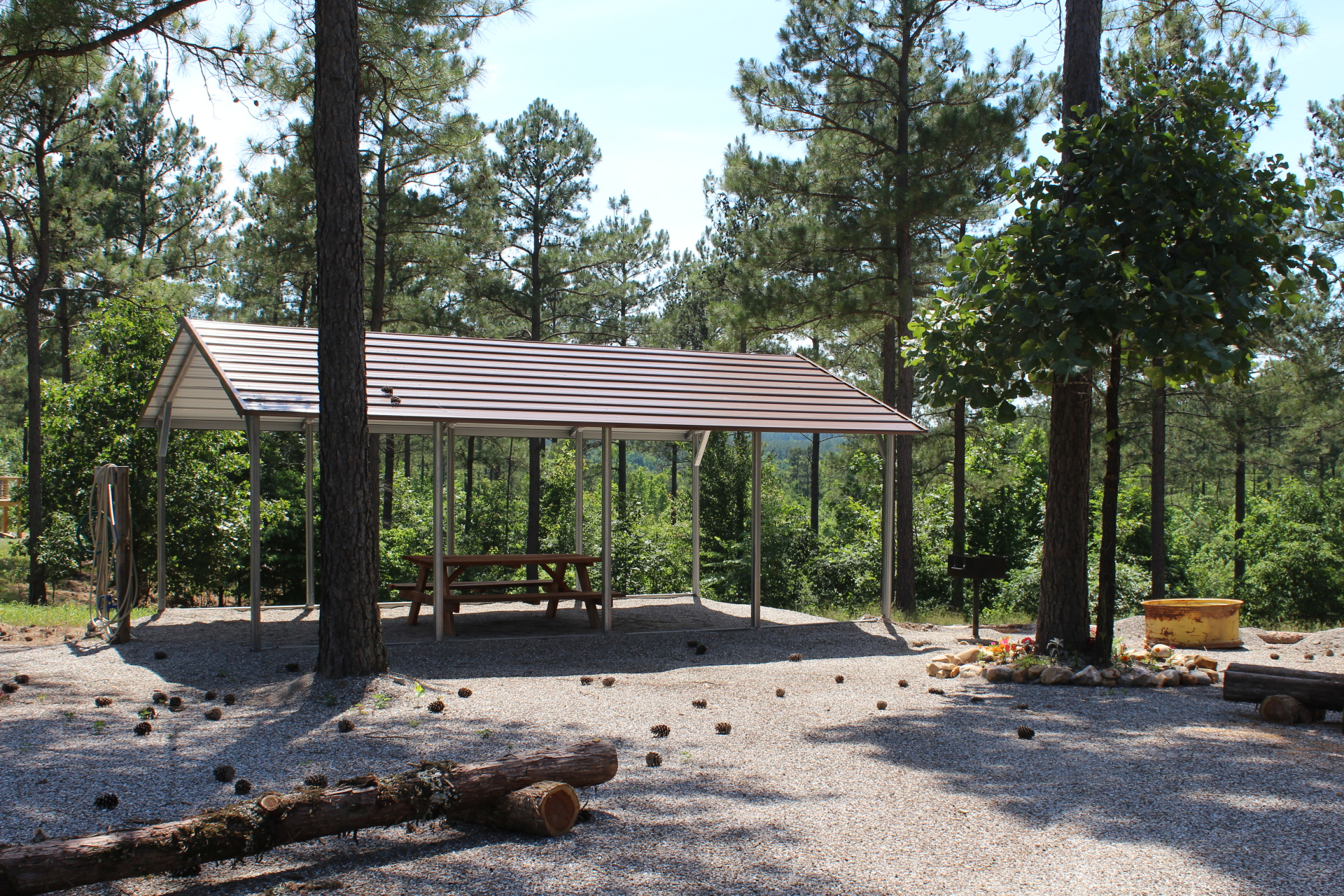 Covered outside picnic area with fire pit, outdoor sink and charcoal grill.