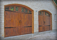 Traditional carriage house Cedar garage doors with butternut stain, hardware, and arched windows.