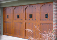 Cedar garage door with butternut stain and speakeasy window guards and iron clavos accents.