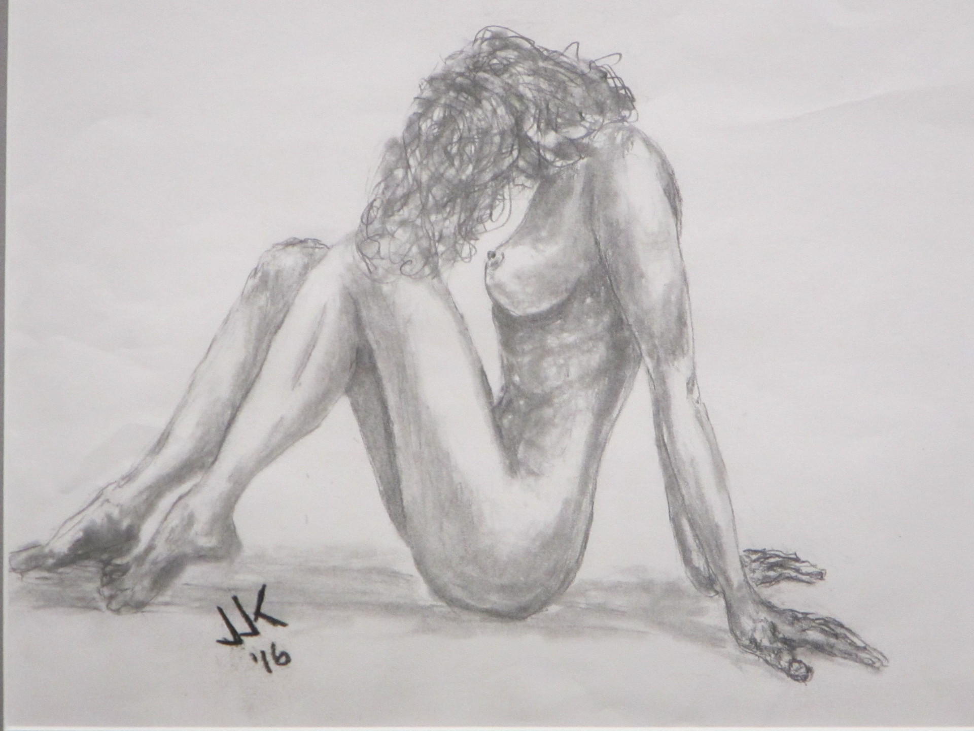 Pencil drawing of a nude woman sitting on the floor with her head forward and her hair over her face.