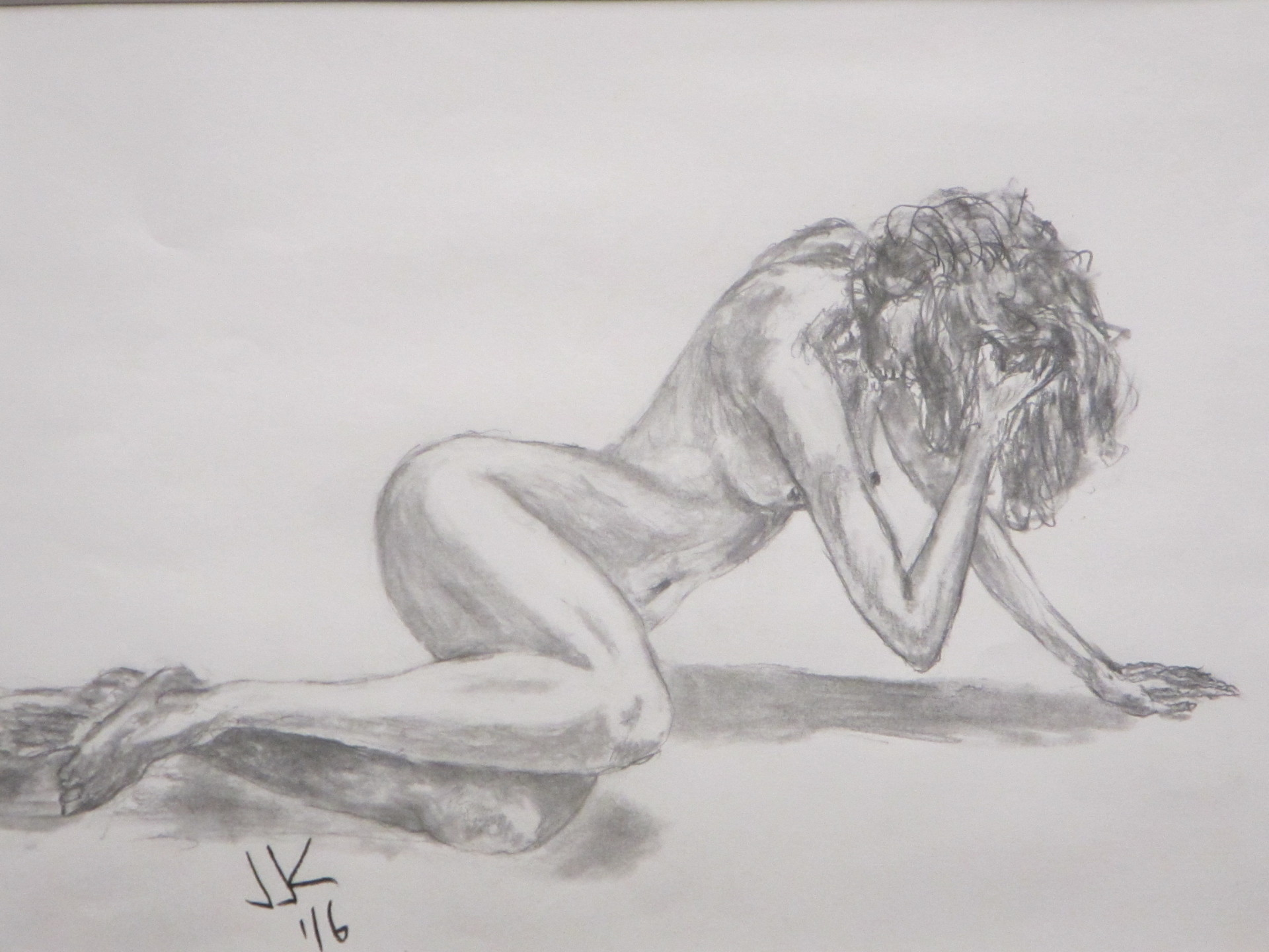 Pencil drawing of a nude woman sitting sideways on the floor and holding her head.
