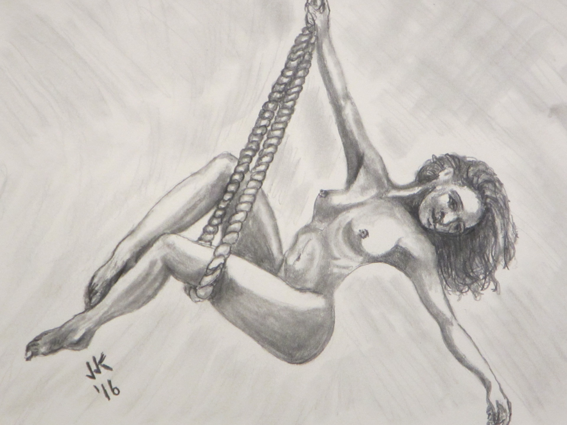 A nude woman swinging from a rope.
