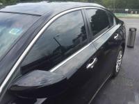 Black Nissan Altima with dark tinted windows