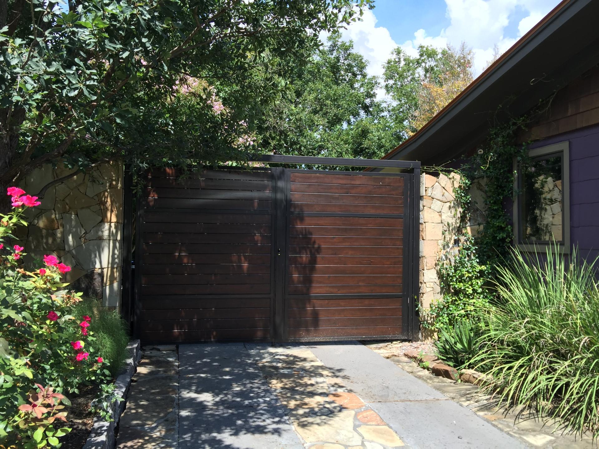 Cedar wood gates with dark oak stain with black steel framing.