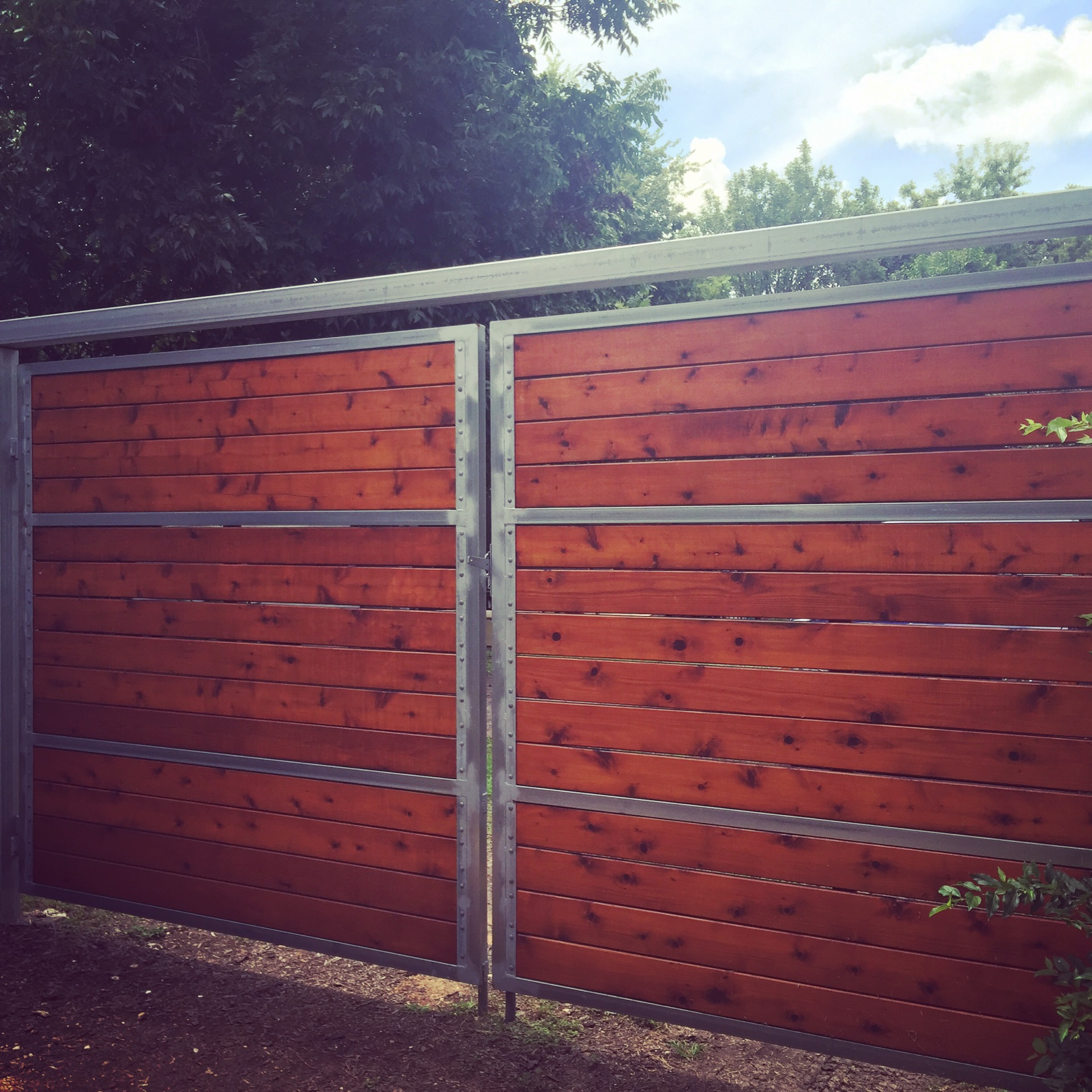 Cedar wood gate with a Teak stain and Galvanized steel frame.