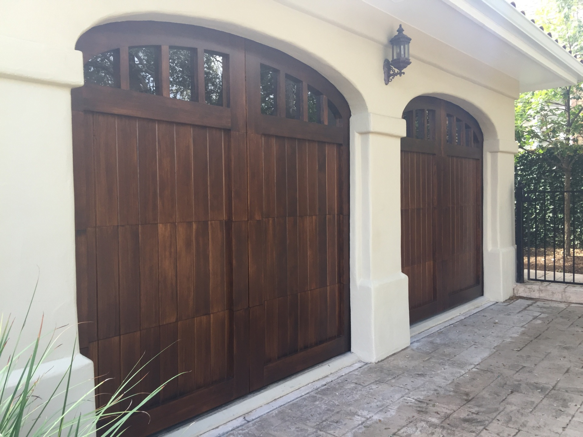 Hemlock garage doors with arched windows and a dark oak stain.