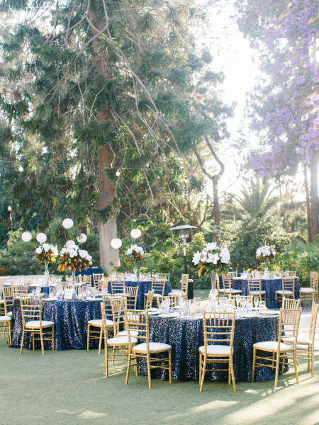 White and gold with blue sequins linens and gold chiavari chairs