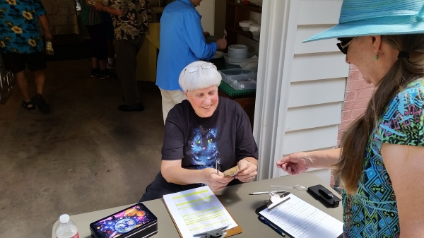 Corlie checks  guests in and accepts donations for the musicians