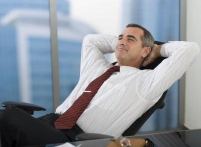 Un homme d'affaire satisfait qui demontre qu'il a l'esprit tranquille a propos de l'informatique dans son entreprise