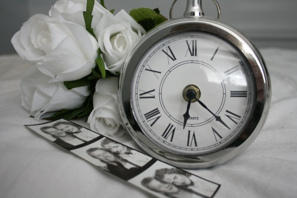A clock, photos and flowers, representing time and memories.