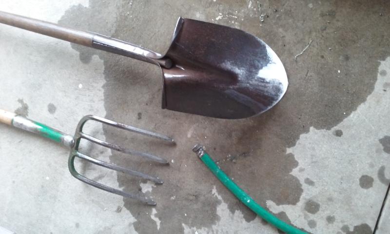 garden hose rinses shovel and pitchfork
