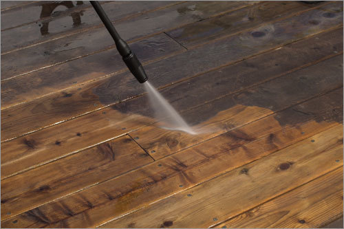 Pressure washer used on a deck, half is dirty and half is cleaned