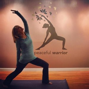 A white woman with graying shoulder-length hair does peaceful warrior pose in front of the peaceful warrior logo.