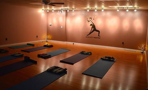 Neatly arranged mats with supplies ready for practice, facing the peaceful warrior image on the far wall.