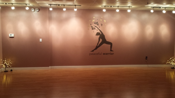Softly lit studio with peaceful warrior image on far wall.