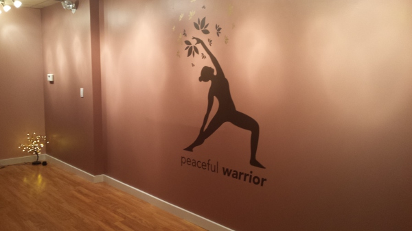 A logo of a woman in peaceful warrior pose on the far wall, lit with soft lighting from above.