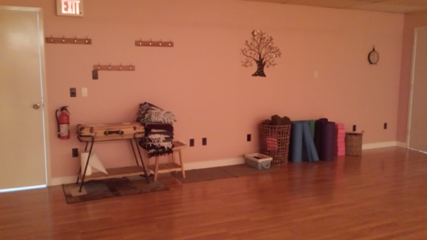 Picture of mats, blankets, straps, and blocks against the entrance wall to the studio.