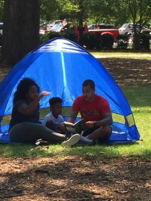 parents read to child in a park tent during a book drive by the Palmetto Optimists