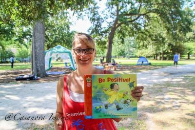 Palmetto Optimist Club member holds up a book titled Be Positive