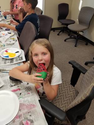 girl pretends to eat painted rock watermelon at the Flash Mob Painting Party