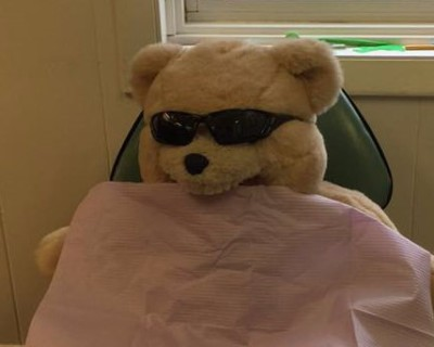 Photo of Teddy Bear with sunglasses and patient napkin