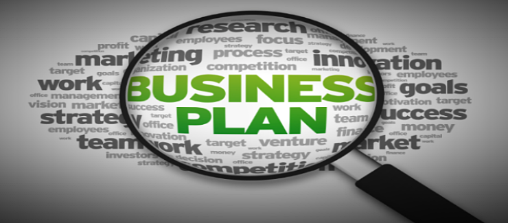 The words business plan enhanced by a magnifying glass.