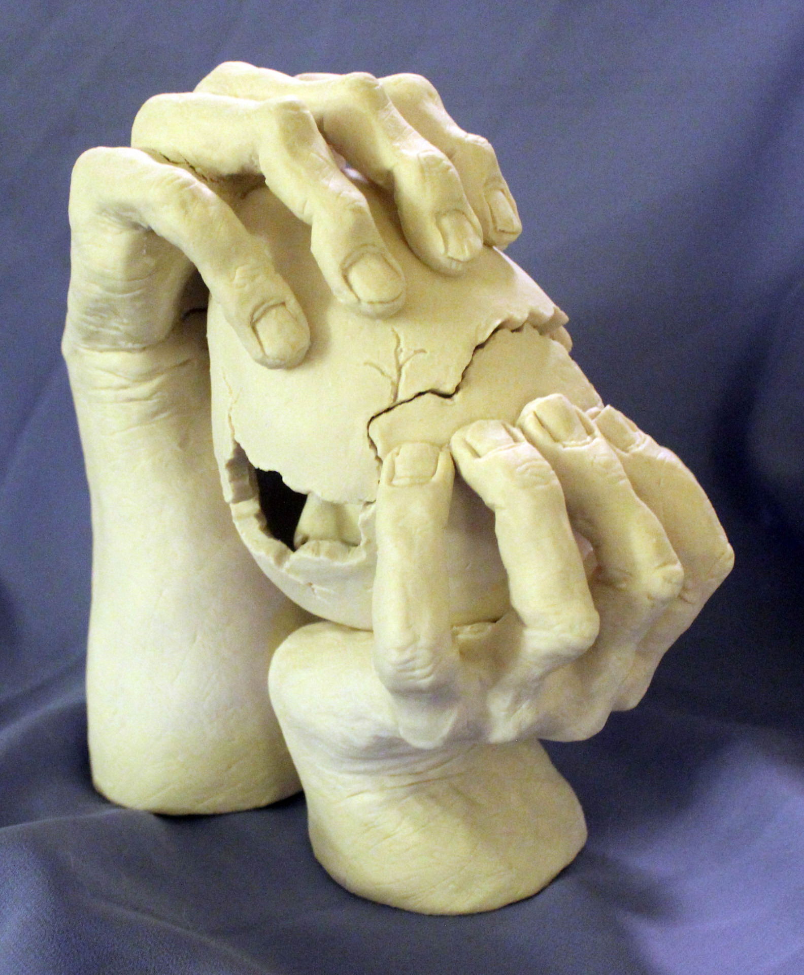 Hands holding cracked egg with creature ceramic sculpture