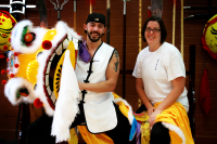 Lion dance image, Mr. Vash and Ms. Ellis pose with the lion